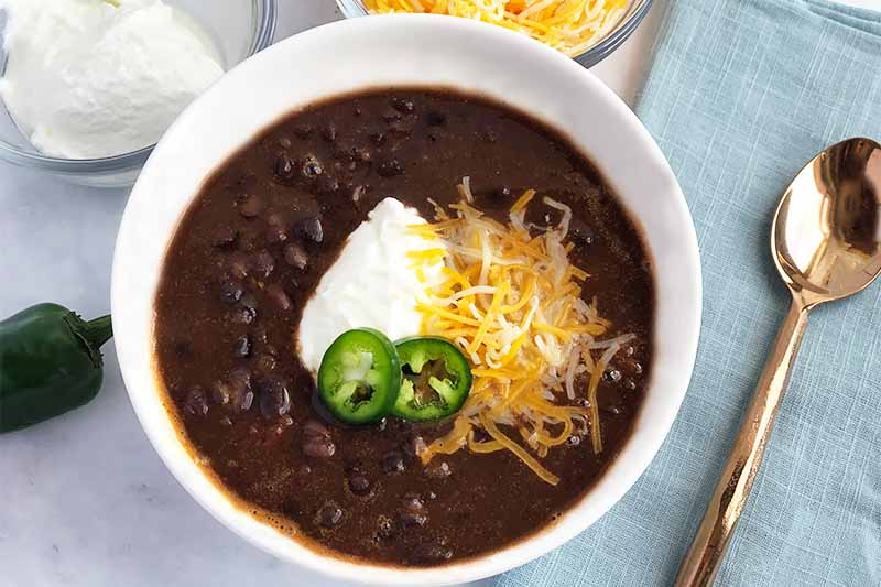 Horizontal image of a white bowl with black bean soup with cheese, sour cream, and jalapeño garnish with a blue napkin and a spoon.