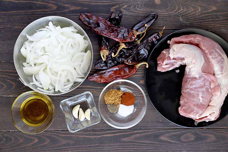 Horizontal image of bowls of sliced onions, spices, garlic, and a plate of raw meat and a pile of dried whole chili peppers.