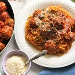 Horizontal image of a plate of pasta and meatballs in a sauce with more of the main dish in a pan in the background next to a bowl of shredded cheese.