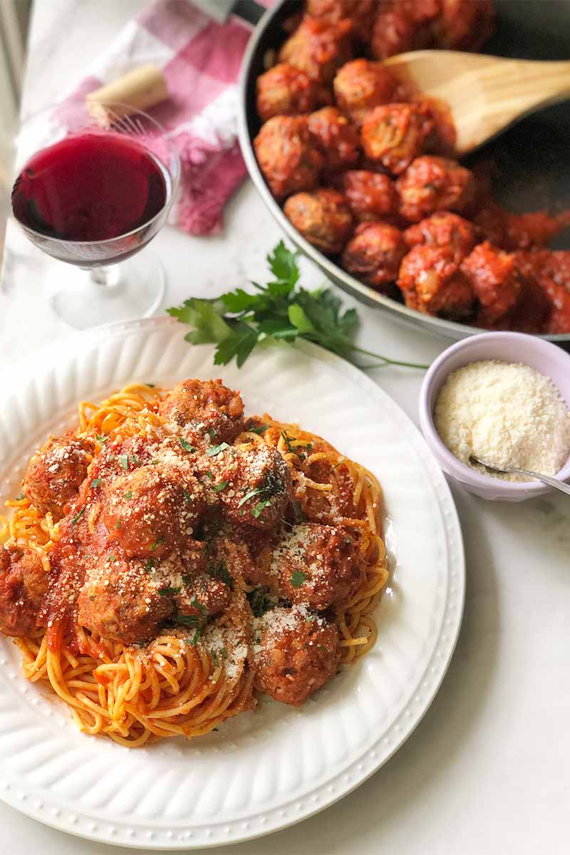 Vertical image of a plate of pasta and meatballs in a sauce with more of the main dish in a pan in the background next to a glass of wine and a bowl of shredded cheese.