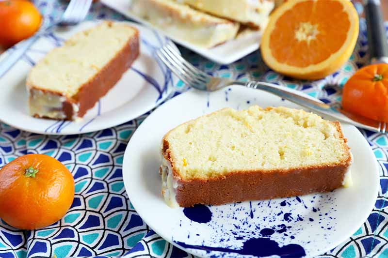 Horizontal image of two slices of pound cake on a white and blue plate, on top of a blue patterned napkin surrounded by whole and sliced citrus and silverware.