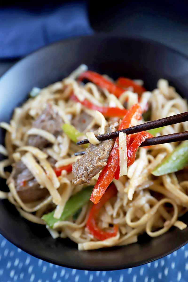 Vertical image of chopsticks holding a piece of meat, bell pepper, and noodles over a big bowl with more of the same dish on top of a blue towel.