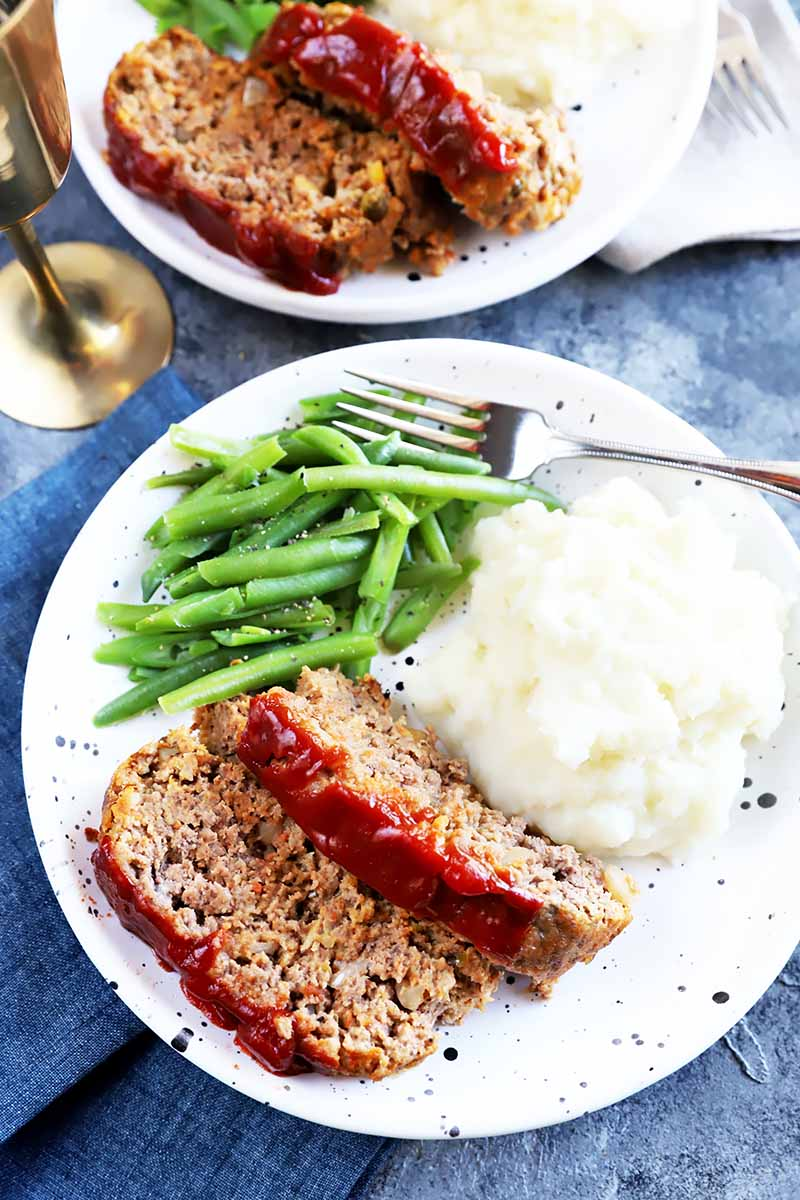 Vertical top-down image of a white plate with green beans, mashed potatoes, and slices of a beef recipe glazed with ketchup.