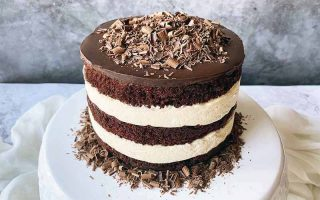 Horizontal image of a layered chocolate and vanilla cake on a cake stand with shaved chocolate.