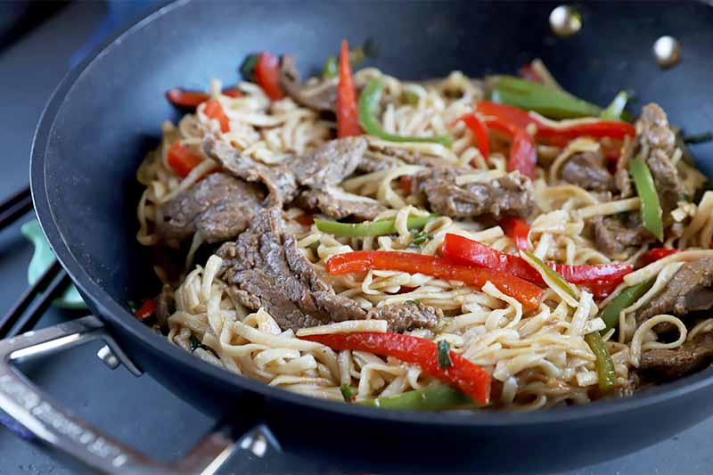 Horizontal image of a dark pan filled with a steak, pepper, and noodle mixture.