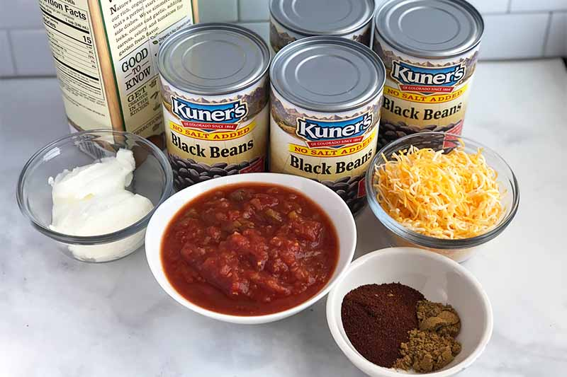 Horizontal image of four cans and bowls of sour cream, salsa, spices, and shredded cheese.
