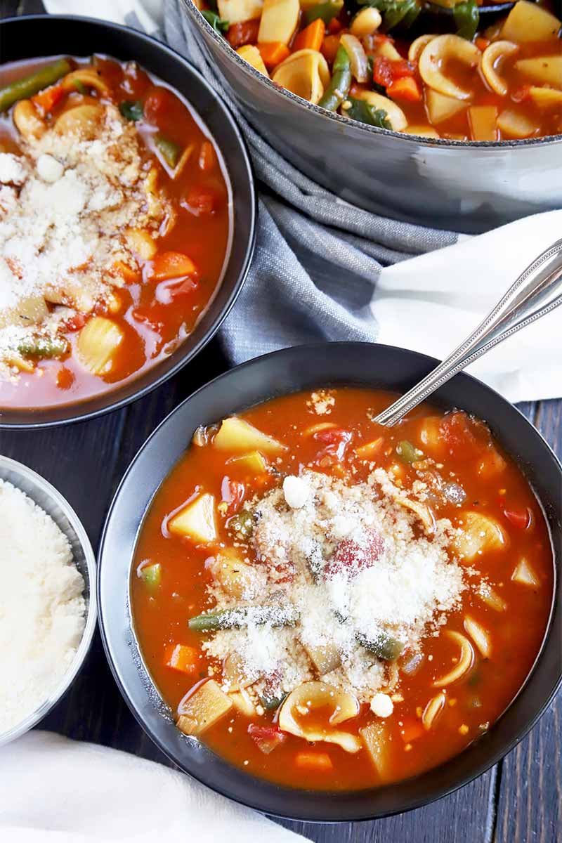 Vertical top-down image of two bowls and a pot filled with a tomato, vegetable, and pasta stew garnished with grated cheese with a spoon inserted into one of the bowls.
