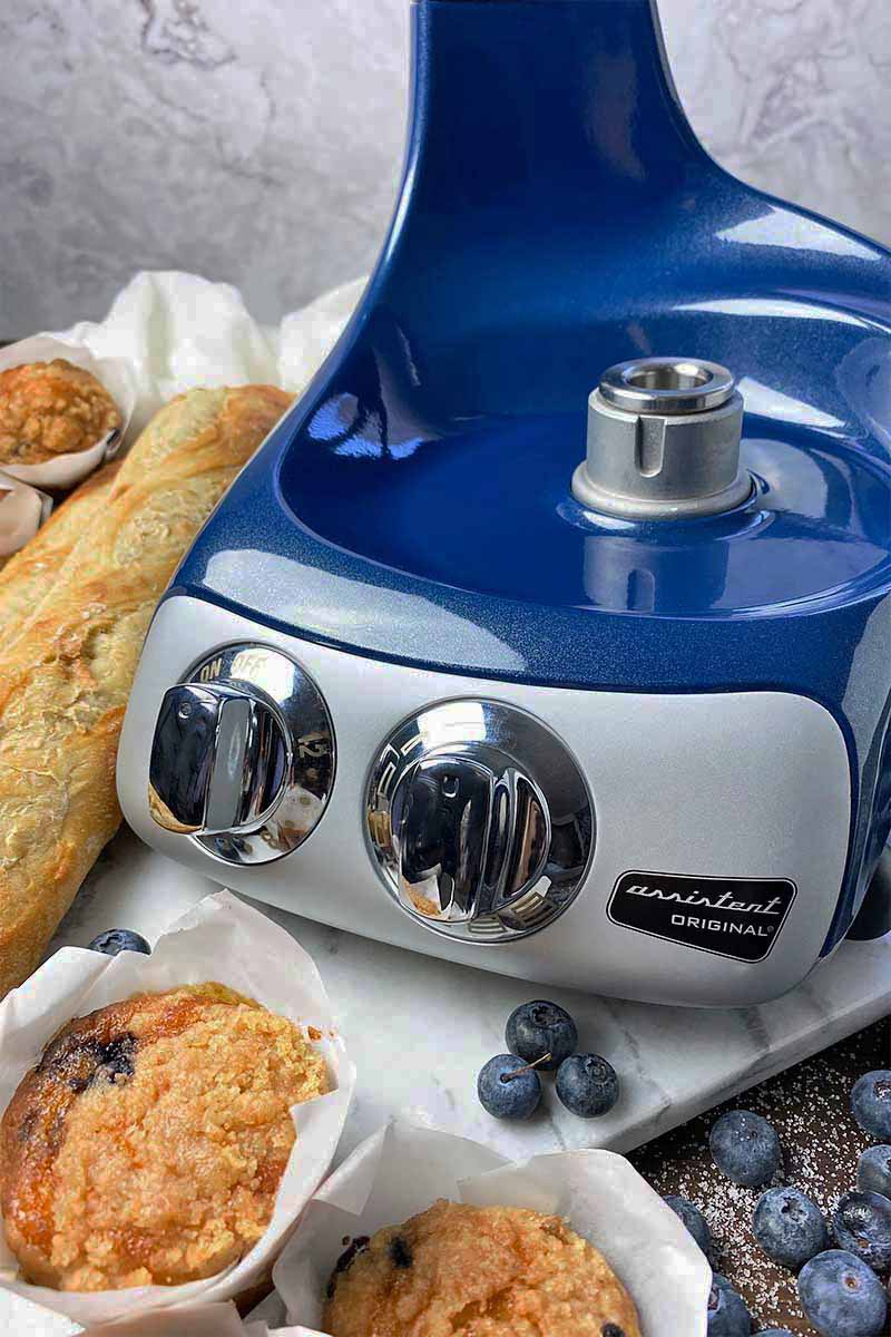Vertical close-up image of the blue base of an appliance on a marble board next to bread, muffins, and blueberries.