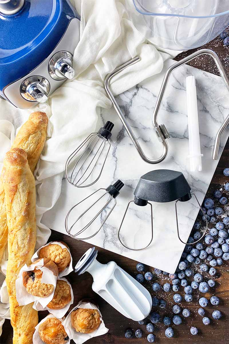 Vertical top-down image of various tools and attachments on a marble board next to a mixer base, bread, muffins, and blueberries.