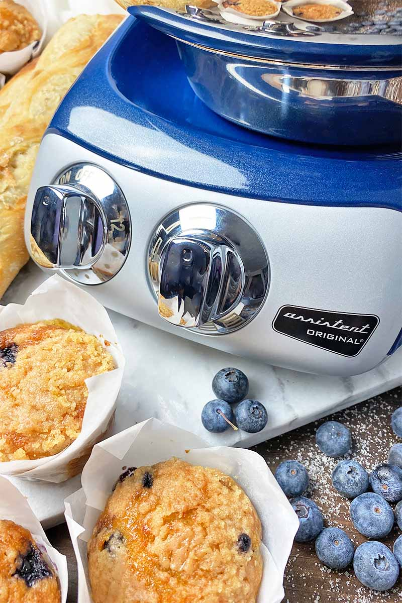 Vertical close-up image of the blue base of an appliance next to muffins and blueberries.