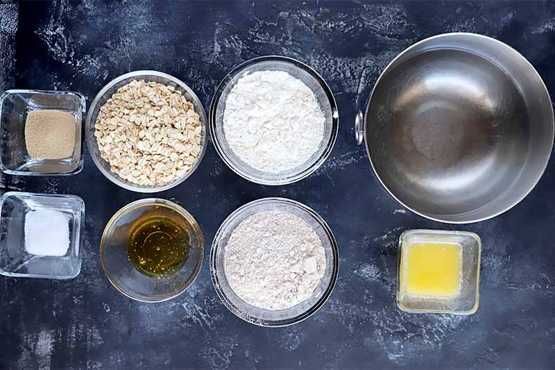 Horizontal image of various wet and dry ingredients in bowls on a dark gray surface.