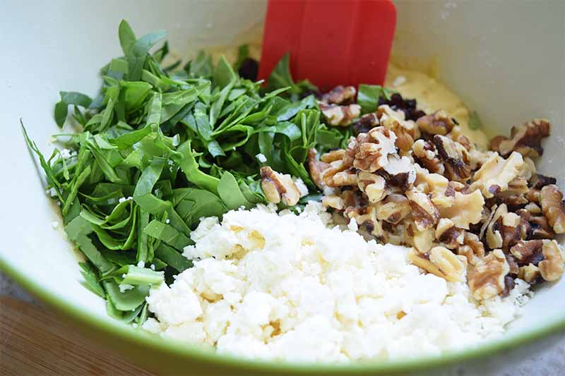Horizontal image of mixing greens, crumbled cheese, and chopped walnuts in a mixture in a bowl with a red spatula.