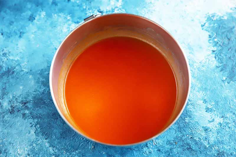 Horizontal image of metal bowl filled with a bright red sauce on a blue table.