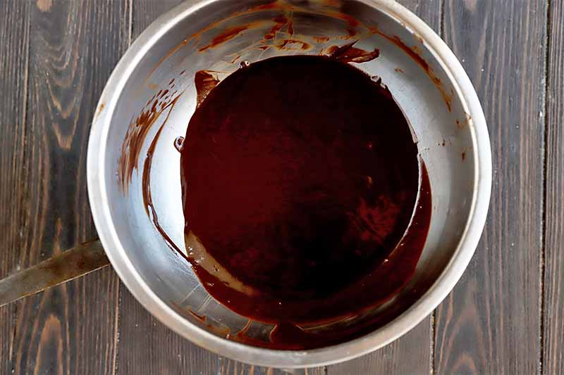 Horizontal image of melted chocolate in a metal bowl.