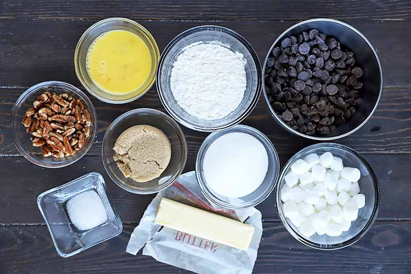 Horizontal image of pecans, eggs, sugar, candy, salt, and chocolate chips in bowls next to a stick of butter on a wooden table.