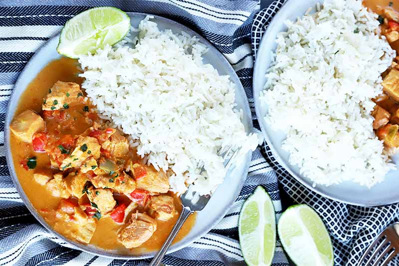 Horizontal top-down image of two blue-trimmed white plates that have a pile of white rice next to an orange meat and vegetable stew on a striped towel next to lime wedges.