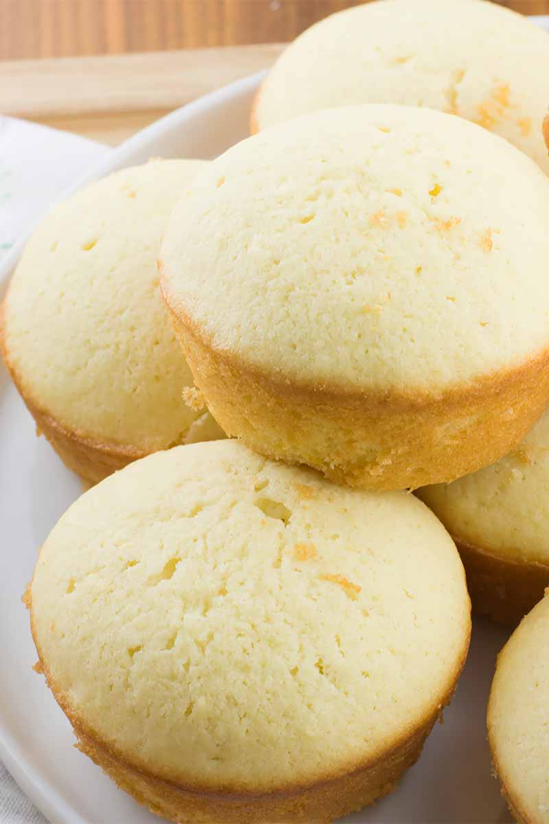 Vertical close-up image of a stack of small, yellow round baked goods on a white plate.