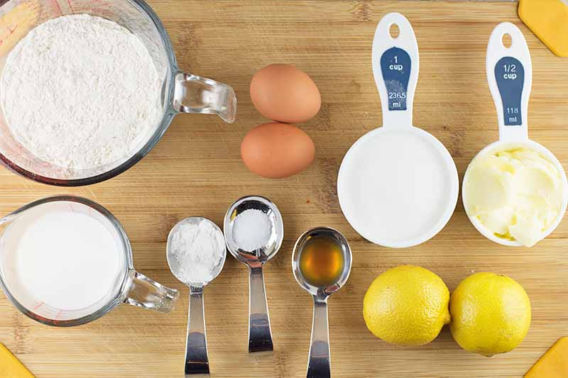 Horizontal image of prepped ingredients on a wooden cutting board to bake lemon baked goods.