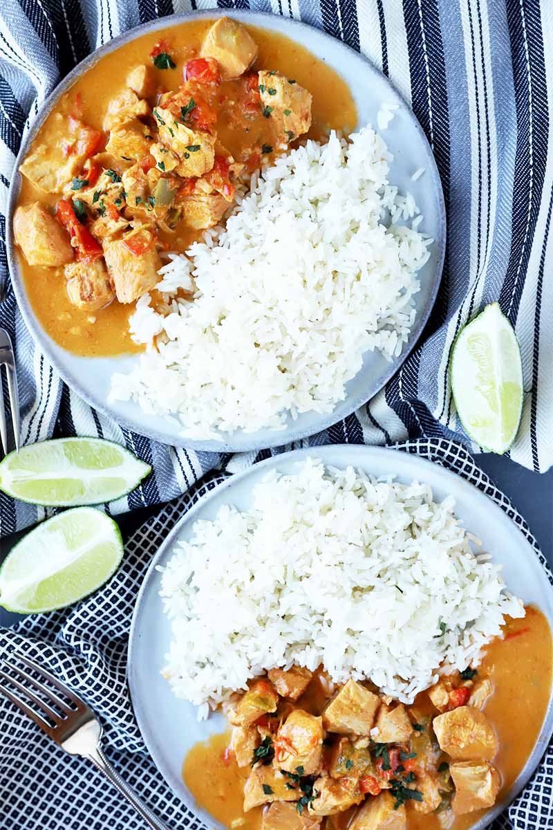 Vertical top-down image of two blue-trimmed white plates that have a pile of white rice next to an orange meat and vegetable stew on a striped towel next to lime wedges.