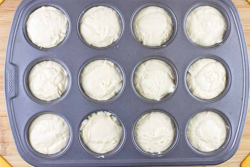Horizontal image of light yellow batter portioned in a muffin pan.