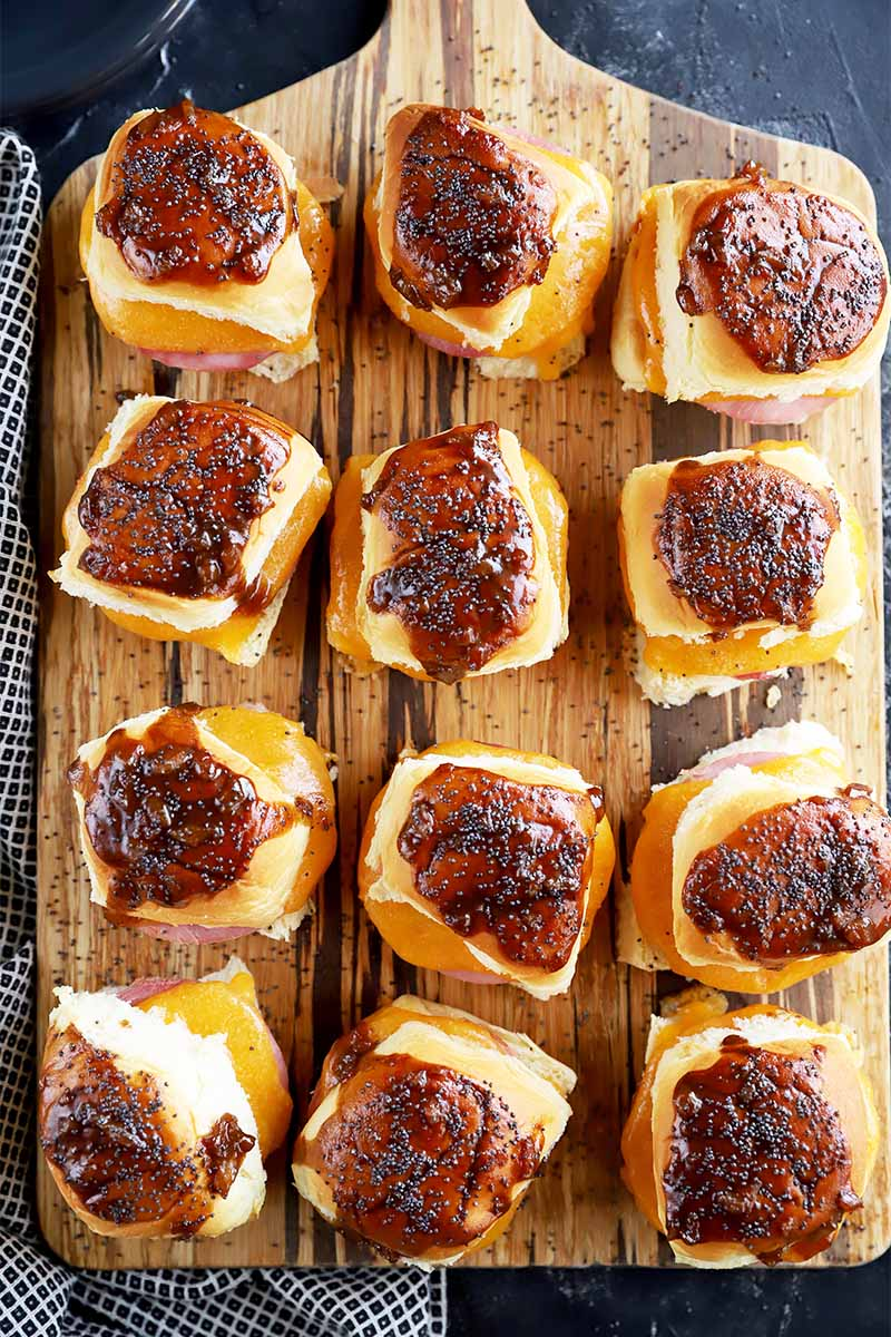 Vertical top down image of a wooden cutting board with rows of mini sandwiches with meat and melted cheddar.