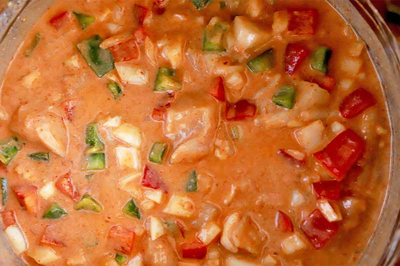 Horizontal image of a mixture of vegetables, poultry pieces, and orange liquid ingredients in a large bowl.