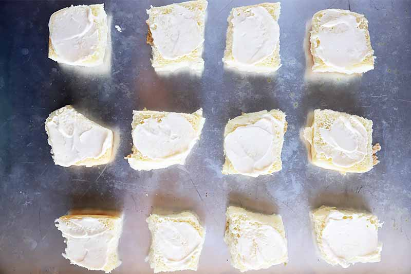 Horizontal image of the bottom halves of rolls spread with mayonnaise.
