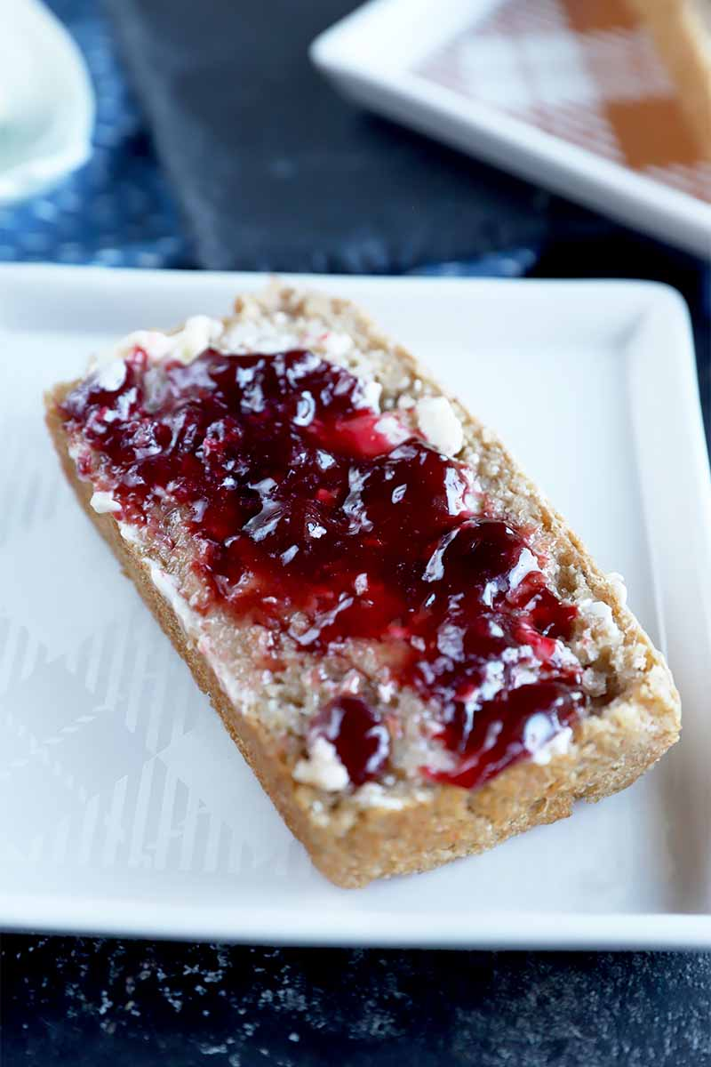 Vertical image of a slice of bread covered in butter and jam.
