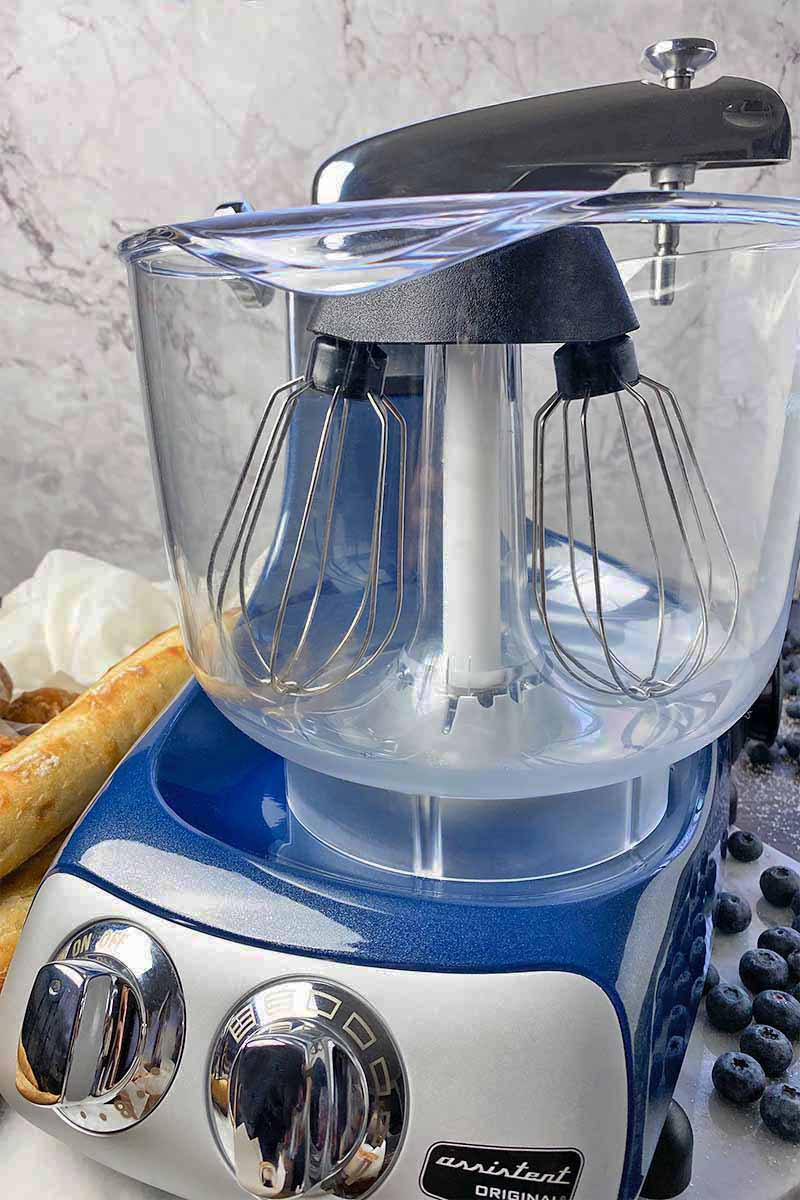 Vertical image of a plastic bowl and whisk attachments on top of a blue motor base.