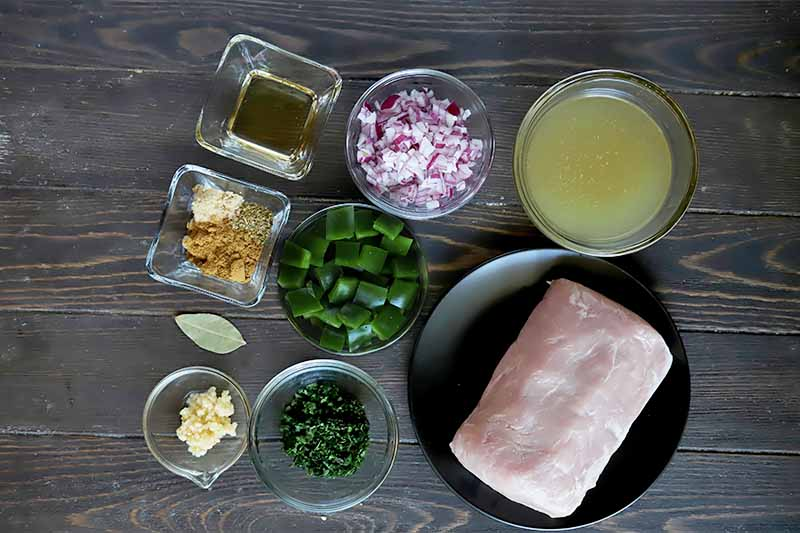 Horizontal image of assorted chopped fresh ingredients and spices in bowls next to a plate of raw meat.