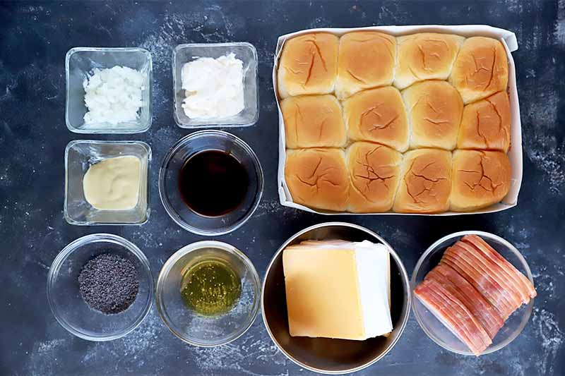 Horizontal image of bowls of prepared ingredients and seasonings next to a tray of Hawaiian rolls.