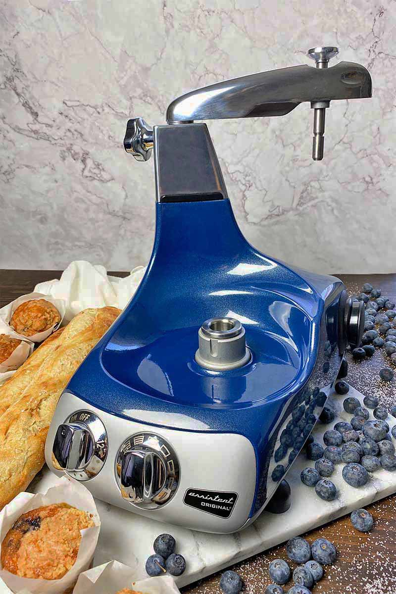 Vertical image of an entire stand mixer in a bright shade of blue on a marble board next to fruit, bread, and muffins.