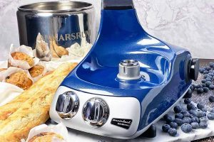 Horizontal image of the base of a blue mixer next to a metal bowl, bread, muffins, and blueberries.