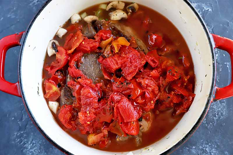 Horizontal image of chopped tomatoes over a large piece of meat and vegetables in a pot.