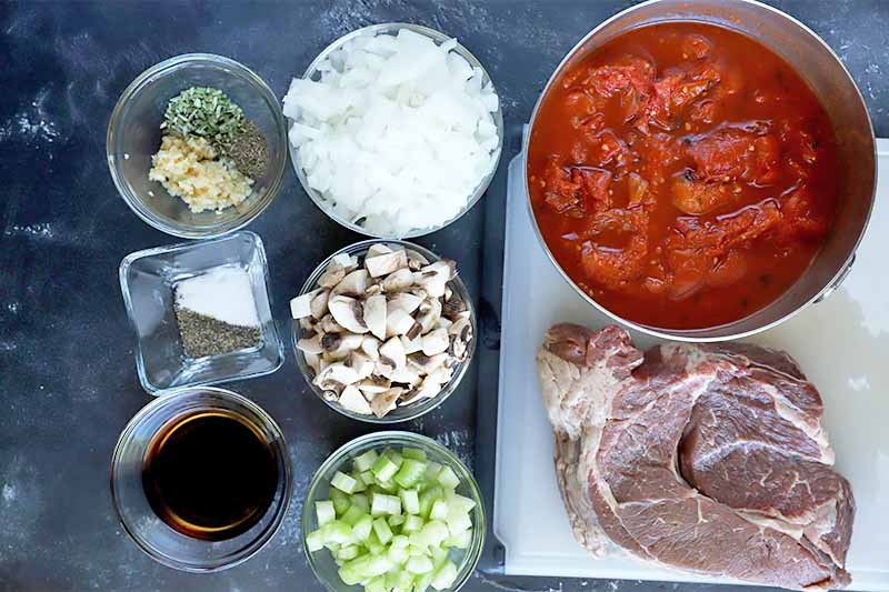 Horizontal image of prepped mushrooms, onions, celery, and tomatoes next to raw meat and seasonings.