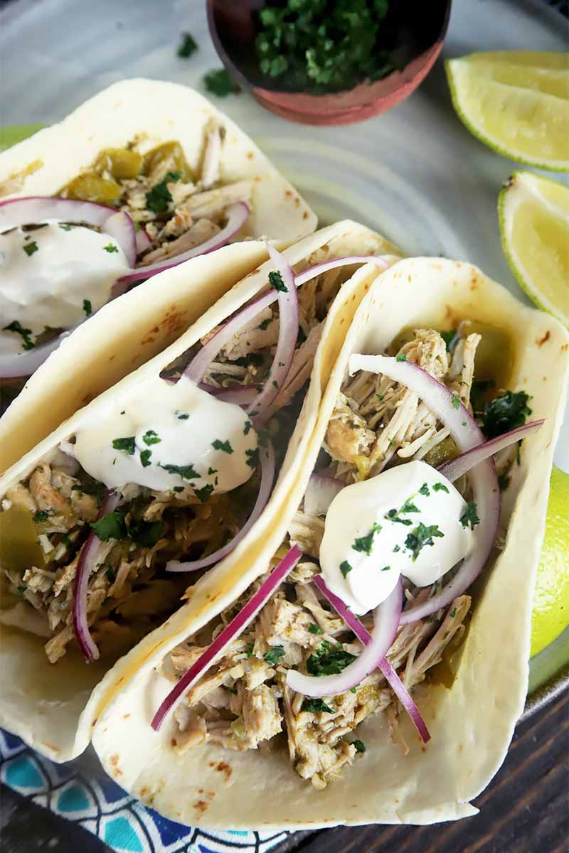 Vertical close-up image of three flour tortillas filled with shredded meat, thinly sliced red onions, and sour cream on a plate.