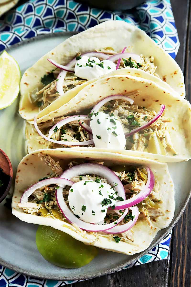 Vertical top-down image of three flour tortillas filled with shredded meat, sour cream, sliced onions, and chopped herbs on a plate on a blue patterned napkin.