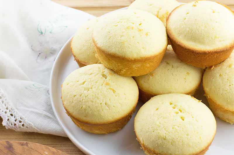 Horizontal image of a stack of round, light yellow, small baked goods on a white plate on a white napkin.
