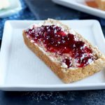 Horizontal image of a slice of bread covered in butter and jam on a white square plate.