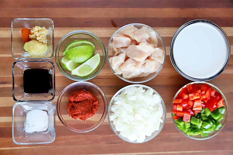 Horizontal image of prepped ingredients for a vegetable and poultry stew.