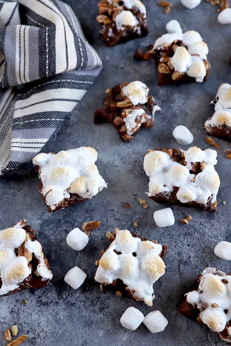 Vertical image of scattered bar cookies topped with toasted white candies next to a gray and white towel.