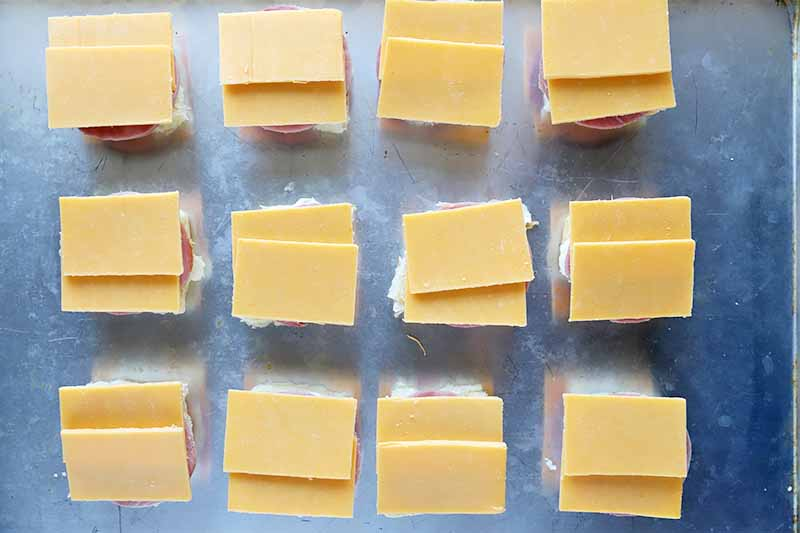 Horizontal image of cheddar slices on top of the bottom halves of rolls.