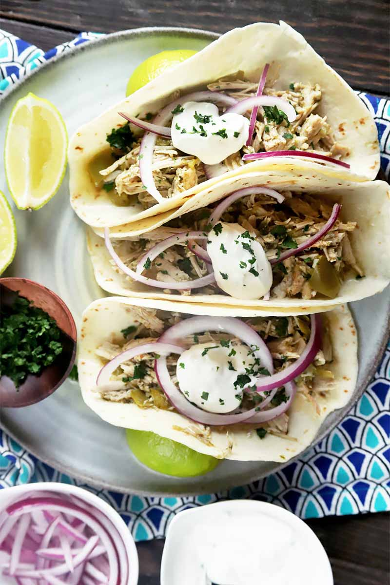 Vertical image of three flour tortillas filled with meat, sour cream, and onions on a plate next to limes and a bowl of sliced onions on a blue napkin.