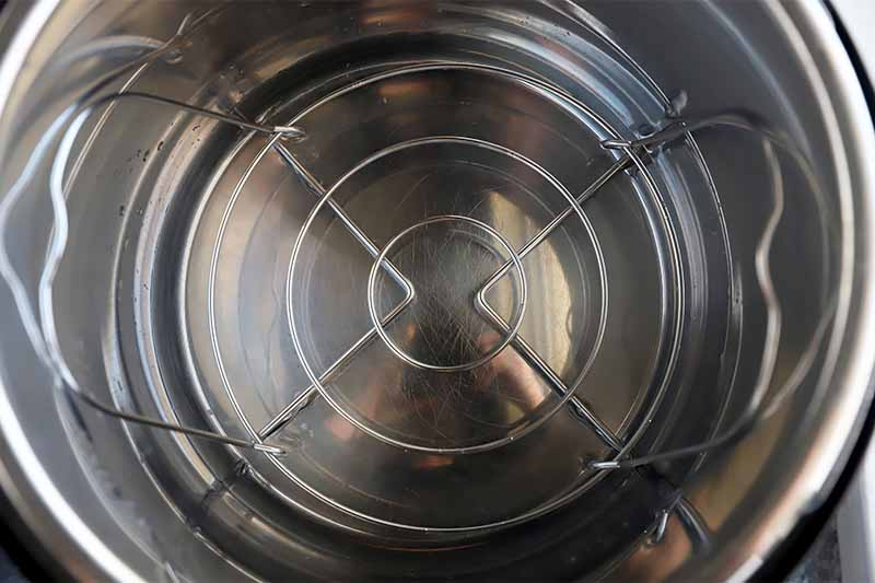 Horizontal image of the inside of an Instant Pot with a steamer insert.