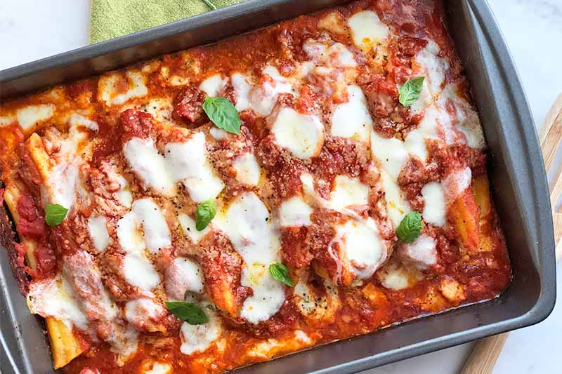 Horizontal image of a rectangular metal baking dish filled with a casserole completely covered in tomato sauce, herbs, and melted mozzarella.