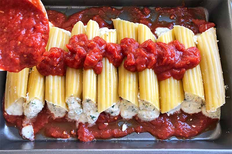 Horizontal image of pouring a chunky tomato sauce over prepared manicotti in a baking pan.