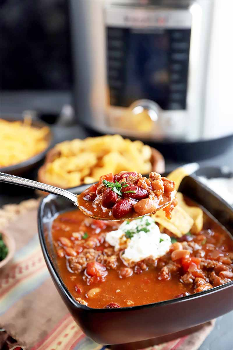 Vertical image of a hearty spoonful of a deep red chunky stew in a black bowl garnished with sour cream and chips in front of a metal kitchen appliance.