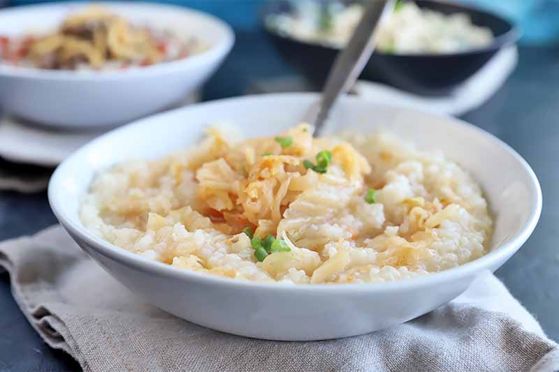 Horizontal image of a white bowl full of a thick stew topped with shredded kimchi and fried onions served with a metal spoon on top of a tan napkin.