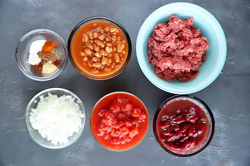 Horizontal image of beans, tomatoes, seasonings, and chopped onions in bowls on a gray surface.