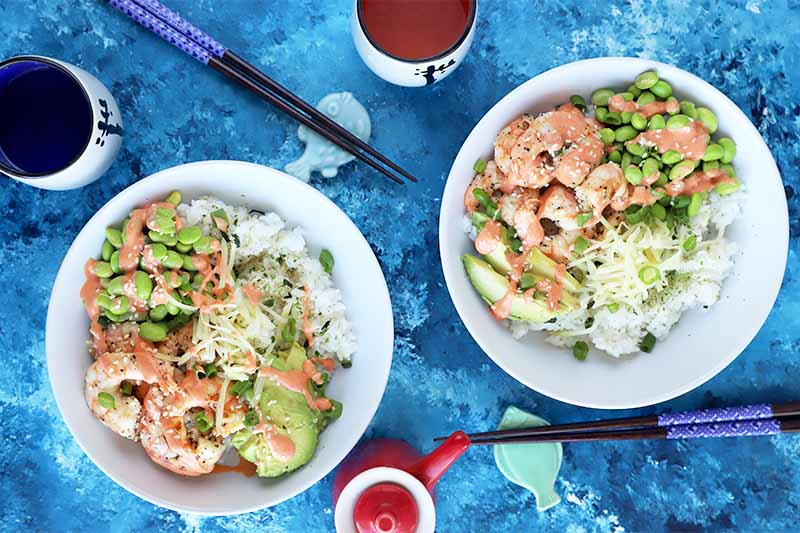 Horizontal image of two white dishes filled with cooked grains, edamame, avocado, cooked seafood, and a drizzle of a red creamy sauce on a blue table next to chopsticks and drinks.